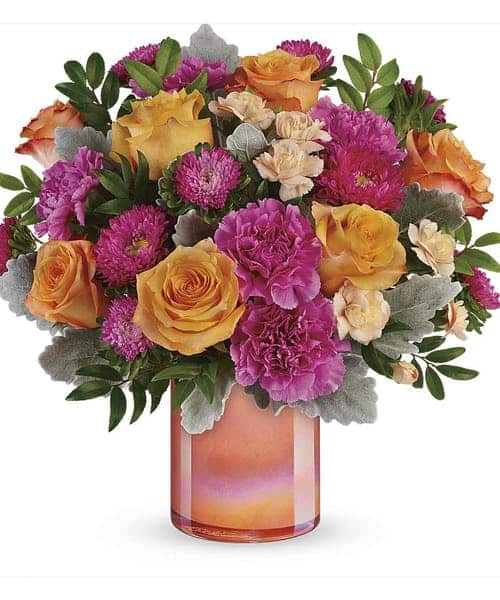 Celebrate spring or any season, with this lush orange and pink bouquet, artfully gathered in a sunset-inspired peach glass vase with shimmering pearlized finish.